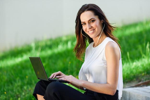 Młoda kobieta pracuje z jej laptopu obsiadaniem na podłoga. Premium Zdjęcia