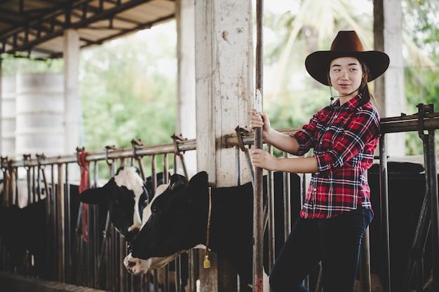 Młoda kobieta pracuje z sianem dla krów na mleczarni gospodarstwie Darmowe Zdjęcia
