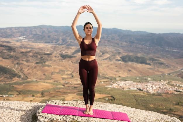 Młoda kobieta praktykujących jogę na szczycie góry Darmowe Zdjęcia