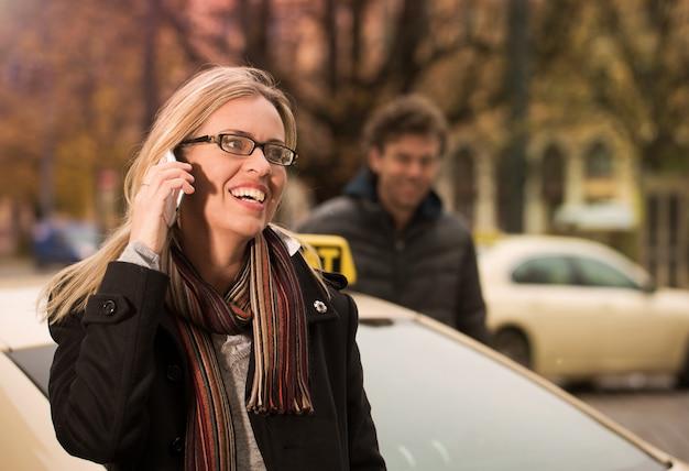 Młoda kobieta przed taxi z telefonem Premium Zdjęcia