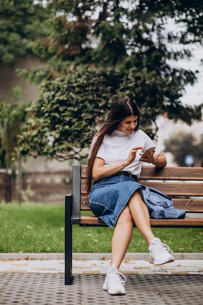 Młoda Kobieta Przy Użyciu Telefonu I Siedząc Na ławce W Parku Darmowe Zdjęcia