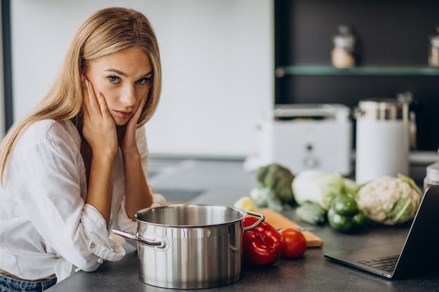 Młoda Kobieta Przygotowuje Jedzenie W Kuchni Darmowe Zdjęcia