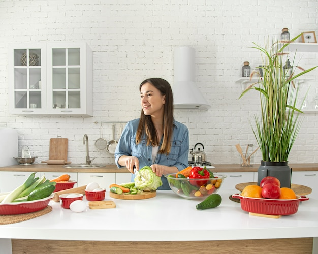 Młoda Kobieta Przygotowuje Sałatkę W Kuchni. Darmowe Zdjęcia