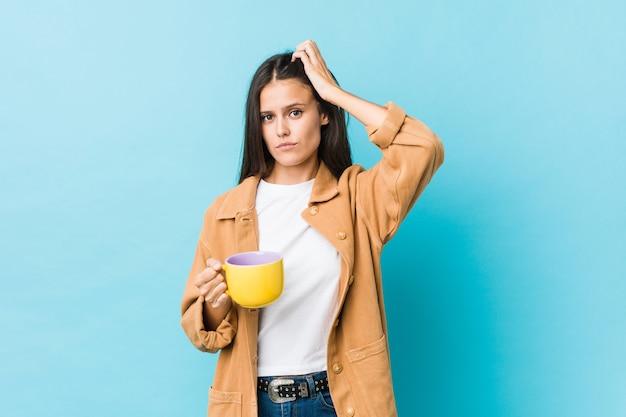 Młoda Kobieta Rasy Kaukaskiej Trzymająca Kubek Kawy, Będąc W Szoku, Przypomniała Sobie Ważne Spotkanie. Premium Zdjęcia