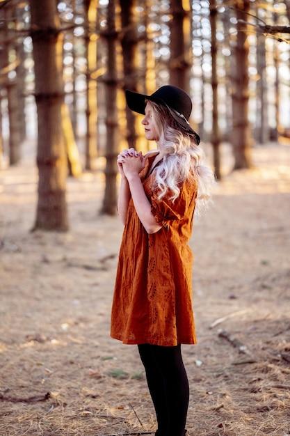 Młoda Kobieta Rasy Kaukaskiej W Stylowym Czarnym Kapeluszu Modląc Się W Malowniczym Lesie, Jesienny Nastrój Darmowe Zdjęcia