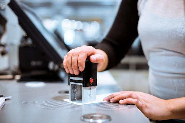 Młoda Kobieta Ręcznie Robi Proces Płatności, Coraz Znaczek Sprzedaży Do Paragonu W Wielkim Centrum Handlowym, Koncepcja Finansów Premium Zdjęcia