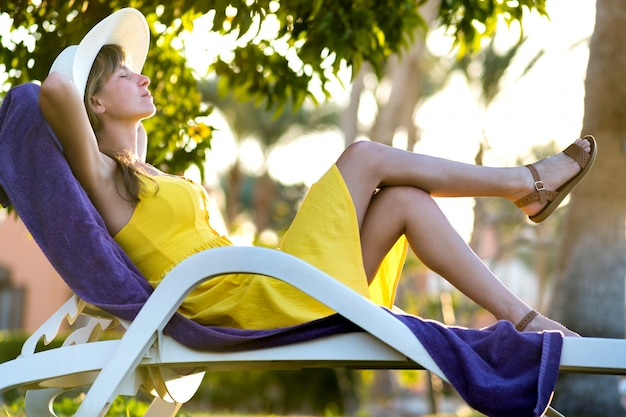 Młoda Kobieta Relaksuje Outdoors Na Pogodnym Letnim Dniu. Szczęśliwa Pani Leżącej Na Wygodne Krzesło Plaży Marzeń Myślenia. Spokojna Piękna Uśmiechnięta Dziewczyna Cieszy Się świeże Powietrze Relaksuje Z Zamkniętymi Oczami. Premium Zdjęcia