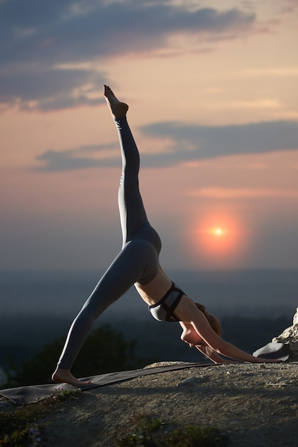 Młoda Kobieta Robi ćwiczenia Jogi Na świeżym Powietrzu O Zachodzie Słońca Premium Zdjęcia