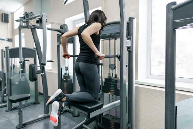 Młoda kobieta robi ćwiczenia na plecy na maszynie fitness Premium Zdjęcia