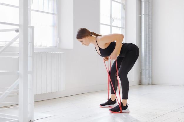 Młoda Kobieta Robi ćwiczenia Oporowe Wioślarza Z Paskiem Mocy W Widoku Z Boku W Wysokiej Siłowni Premium Zdjęcia