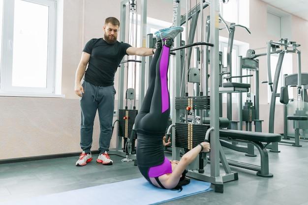 Młoda kobieta robi ćwiczenia rehabilitacyjne z osobistym instruktorem Premium Zdjęcia