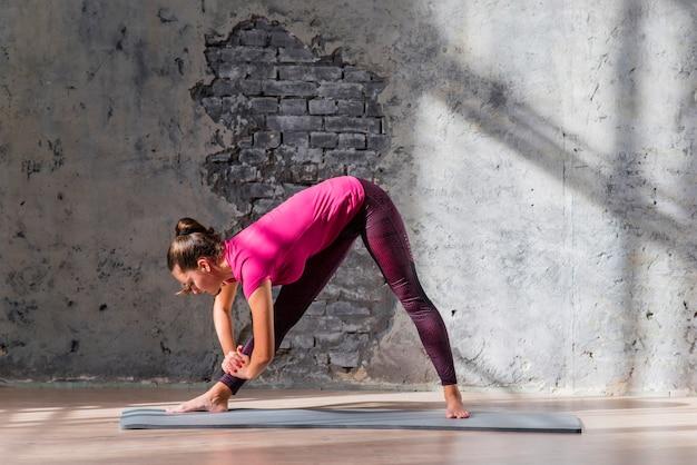 Młoda kobieta robi rozciągania ćwiczeniu w joga klasie Darmowe Zdjęcia