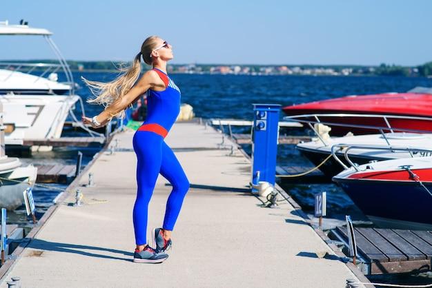 Młoda kobieta robi sportom przy dokiem Premium Zdjęcia