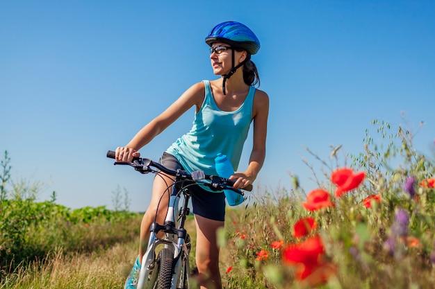 Młoda Kobieta Rowerzysta Jedzie Bicykl W Lato Maczka Polu. Sprawny Dziewczyna Cieszy Się Krajobraz. Premium Zdjęcia