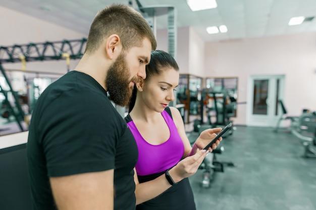 Młoda Kobieta Rozmawia Z Osobistym Trenerem W Siłowni Premium Zdjęcia