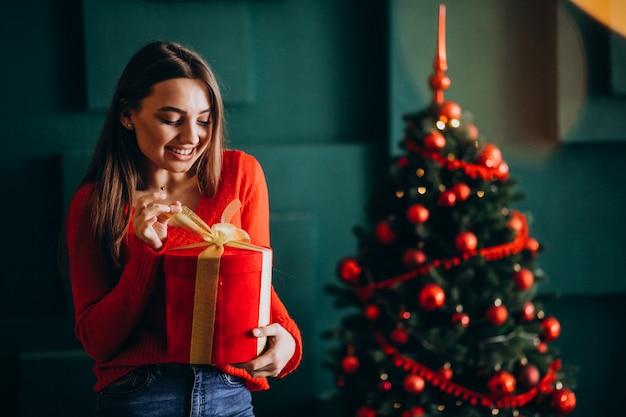 Młoda kobieta rozpakowywanie prezentu przez choinkę Darmowe Zdjęcia