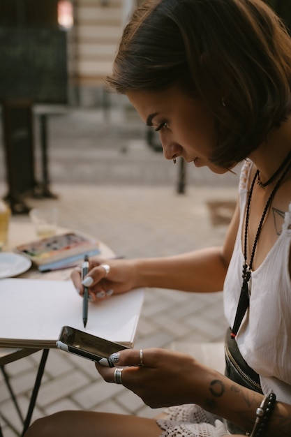 Młoda Kobieta Rysuje Ołówkiem Na Zewnątrz Ołówkiem Na Zewnątrz Darmowe Zdjęcia