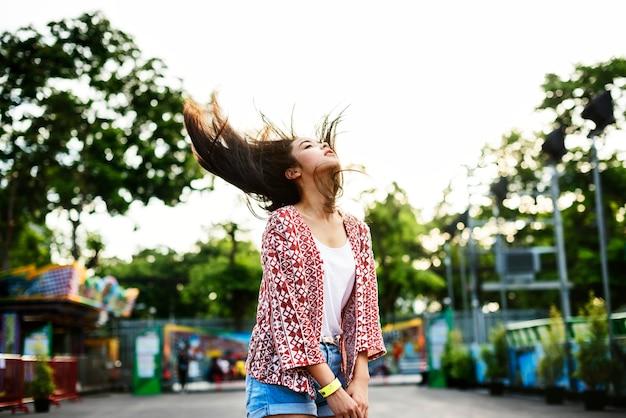 Młoda kobieta rzuca jej włosy przy parkiem rozrywki Premium Zdjęcia
