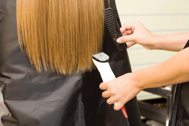 Młoda Kobieta ściąga Włosy Maszynką Do Strzyżenia. Fryzjer. Premium Zdjęcia