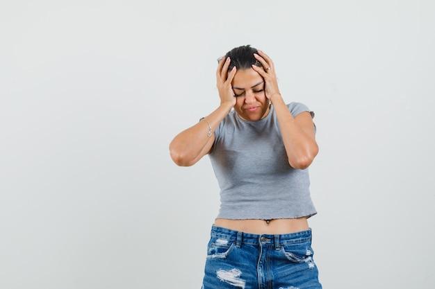 Młoda Kobieta ściskająca Głowę W Dłonie W T-shirt, Szorty I Wyglądająca Na Zmęczoną. Darmowe Zdjęcia