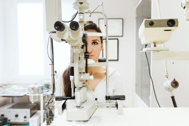 Młoda Kobieta Siedząca W Klinice Okulisty, Aby Zbadać Oczy Przez Profesjonalistę. Premium Zdjęcia