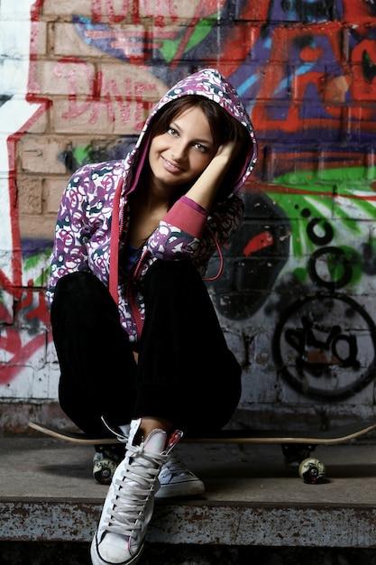 Młoda Kobieta Siedzi Na Deskorolce Darmowe Zdjęcia