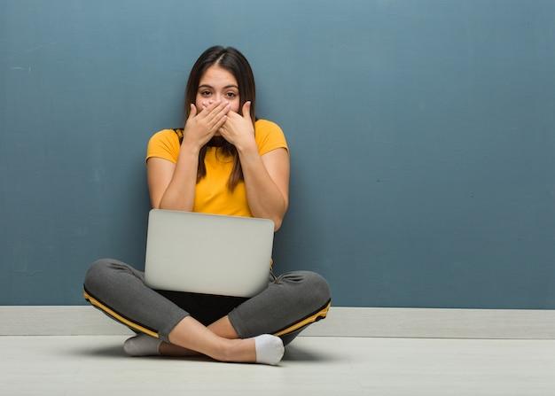 Młoda kobieta siedzi na podłodze z laptopem zaskoczony i zszokowany Premium Zdjęcia