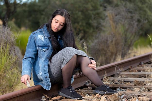 Młoda Kobieta Siedzi Na Torze Pociągu, Pisząc Z Kamienia. Premium Zdjęcia