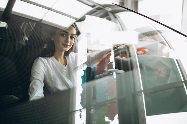 Młoda kobieta siedzi w samochodzie w salonie samochodowym Darmowe Zdjęcia