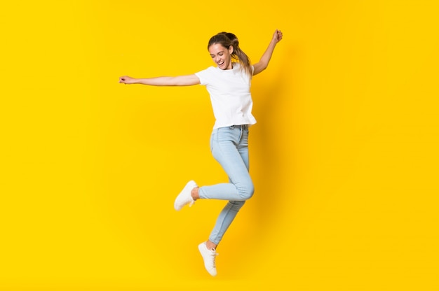 Młoda kobieta skacze nad odosobnioną kolor żółty ścianą Premium Zdjęcia
