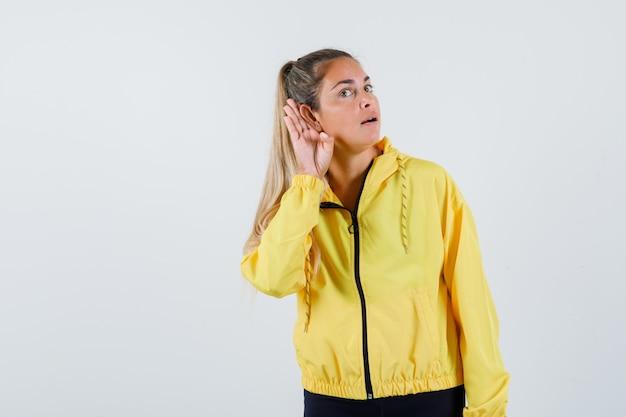 Młoda Kobieta Słucha W żółtym Płaszczu I Patrząc Skoncentrowany Darmowe Zdjęcia