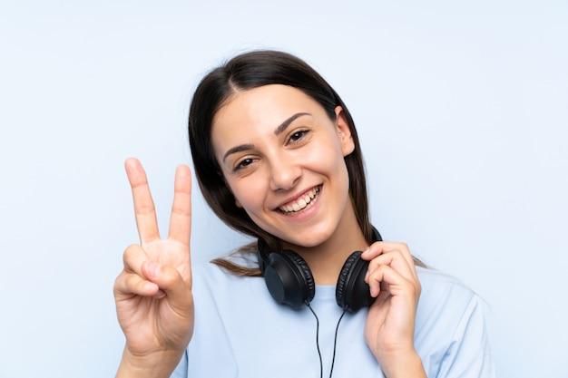 Młoda kobieta słuchania muzyki na izolowanych niebieską ścianą Premium Zdjęcia