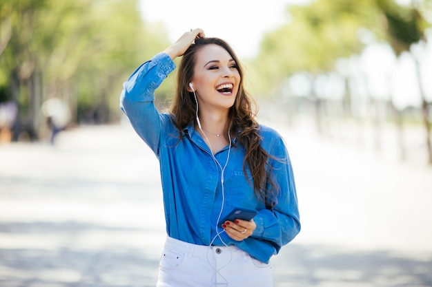 Młoda Kobieta, Słuchanie Muzyki W Słuchawkach Na Ulicy Latem Darmowe Zdjęcia