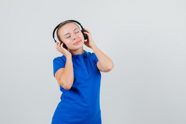Młoda Kobieta, Słuchanie Muzyki W Słuchawkach W Niebieskiej Koszulce Darmowe Zdjęcia