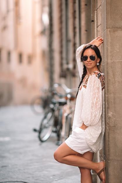 Młoda kobieta spacerująca po opuszczonych ulicach europy. Premium Zdjęcia