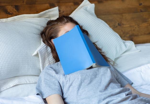 Młoda kobieta śpi na łóżku z książką Premium Zdjęcia
