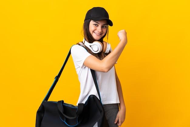 Młoda Kobieta Sport Z Torbą Sportową Na Białym Tle Na żółtej ścianie Robi Silny Gest Premium Zdjęcia