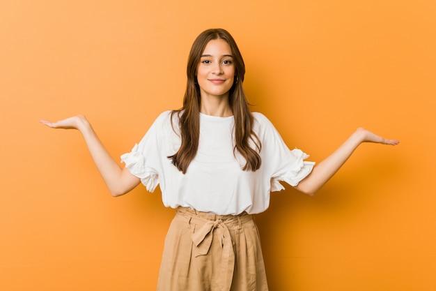 Młoda Kobieta Sprawia, że Waga Z Broni, Czuje Się Szczęśliwa I Pewna Siebie Premium Zdjęcia