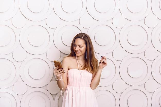 Młoda Kobieta Stoi I Słuchanie Muzyki W Słuchawkach Patrzeć Na Smartphone Premium Zdjęcia