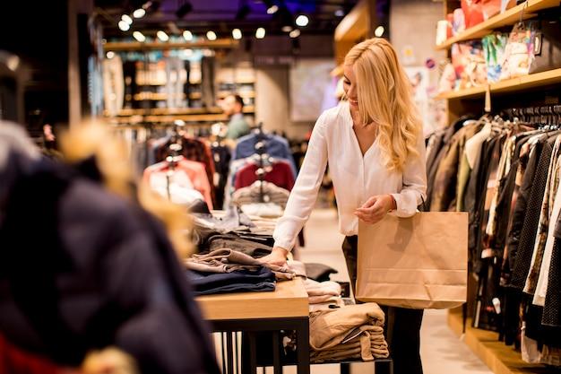 Młoda kobieta stoi przy sklepem odzieżowym z torba na zakupy Premium Zdjęcia