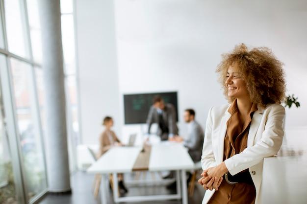 Młoda Kobieta Stojąc W Nowoczesnym Biurze Premium Zdjęcia