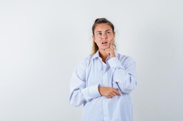 Młoda Kobieta Stojąca W Myśleniu Poza, Opierając Policzek Na Palcu Wskazującym W Białej Koszuli I Patrząc Zamyślony Darmowe Zdjęcia