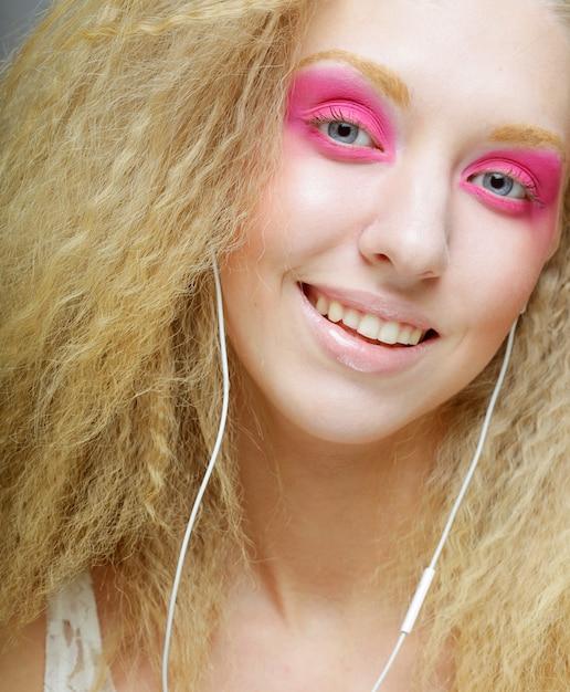 Młoda kobieta tańczy do muzyki na słuchawkach Premium Zdjęcia