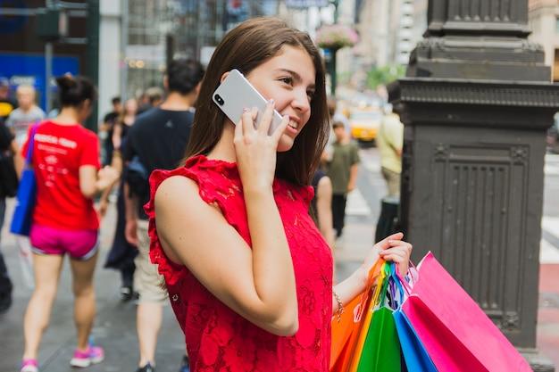 Młoda kobieta telefonuje z torba na zakupy Darmowe Zdjęcia