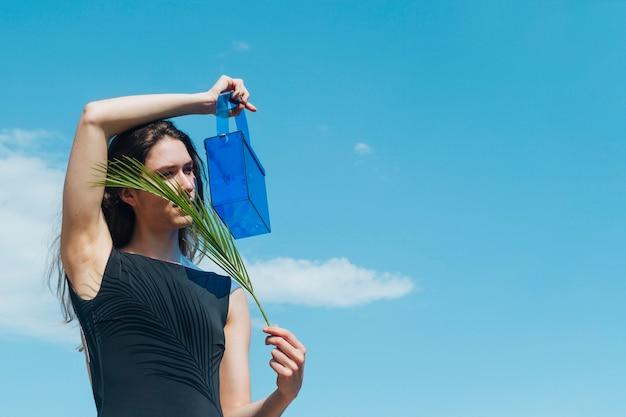 Młoda Kobieta Trzyma Błękitną Plastikową Torbę I Palmowych Liście Przed Jej Twarzą Darmowe Zdjęcia
