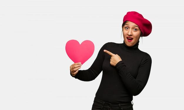 Młoda kobieta trzyma coś z ręką w valentines dniu Premium Zdjęcia