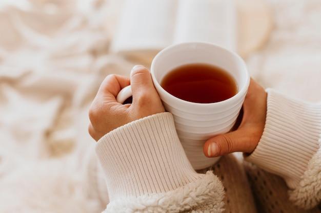 Młoda Kobieta Trzyma Filiżankę Herbaty, Ciesząc Się Ferie Zimowe Darmowe Zdjęcia