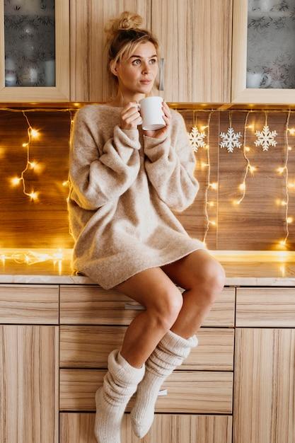 Młoda Kobieta Trzyma Filiżankę Herbaty W Przytulnych Ubraniach Premium Zdjęcia
