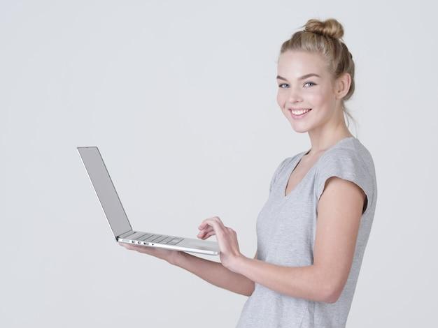 Młoda Kobieta Trzyma Laptopa W Habds. Uśmiechnięta Dziewczynka Kaukaski Z Notatnikiem Pozowanie W Studio Darmowe Zdjęcia