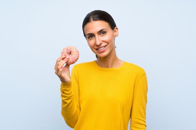 Młoda kobieta trzyma pączek nad odosobnioną błękit ścianą ono uśmiecha się dużo Premium Zdjęcia